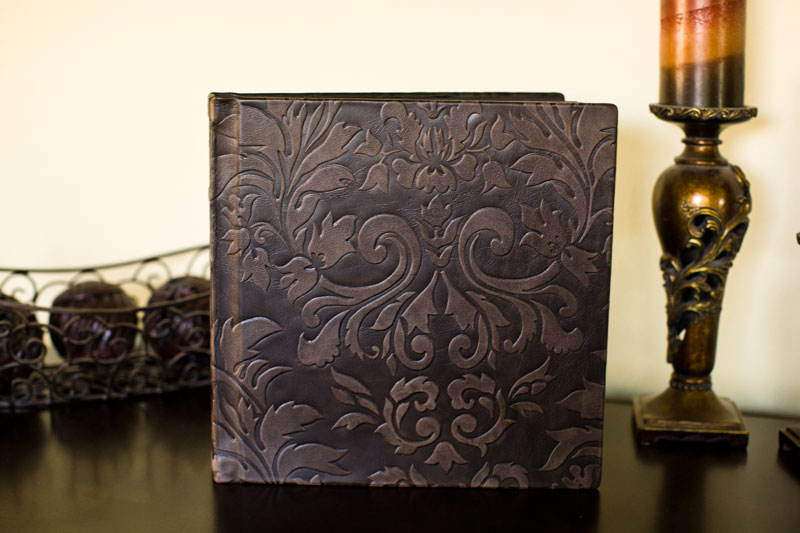 Brown leather wedding album cover with a raised floral design.