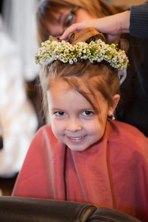 Cute flower girl getting her hair done before the wedding.