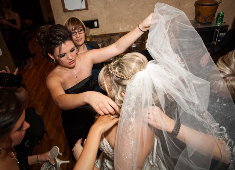 Bridesmaids helping the bride with her veil.