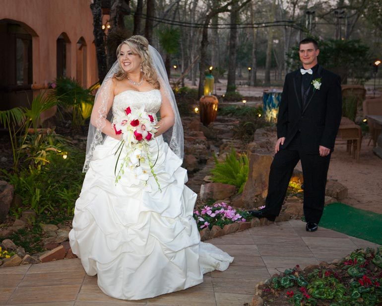 Sexy Bride with her groom looking at her in the background in KAty TX.