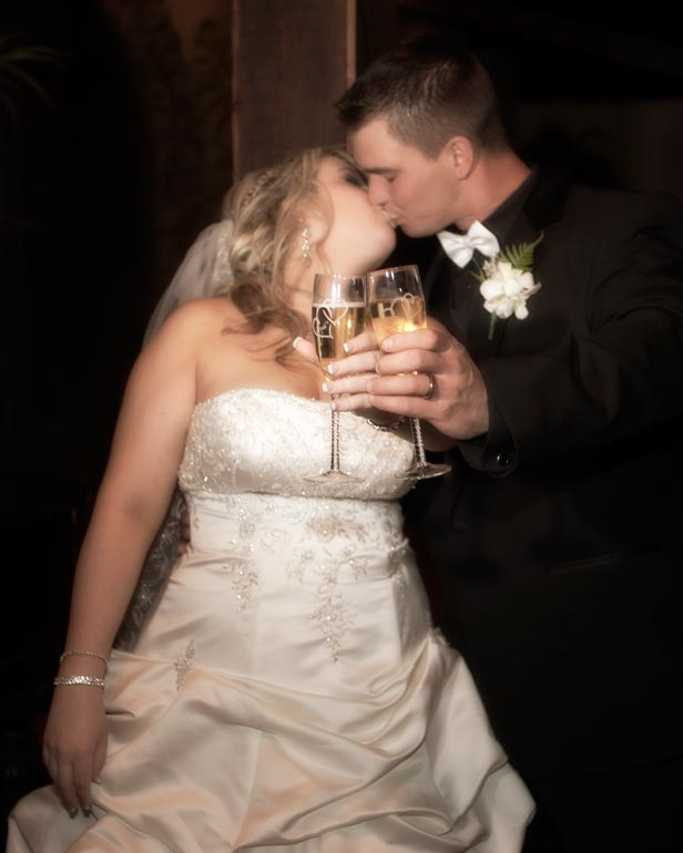 Bride and groom kissing after their wedding toast.